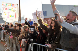Sailors' families and friends wave to loved ones returning on board Royal Navy warships HMS St Albans and HMS Edinburgh at Portsmouth Naval Base