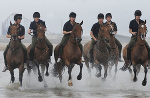 Horses from the King's Troop Royal Horse Artillery exercising on the beach in the shadow of the world-famous Blackpool Tower