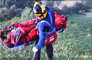 An RAF Search and Rescue crewman and the 74-year-old walker are winched up to the Sea King helicopter at Helvellyn Fell
