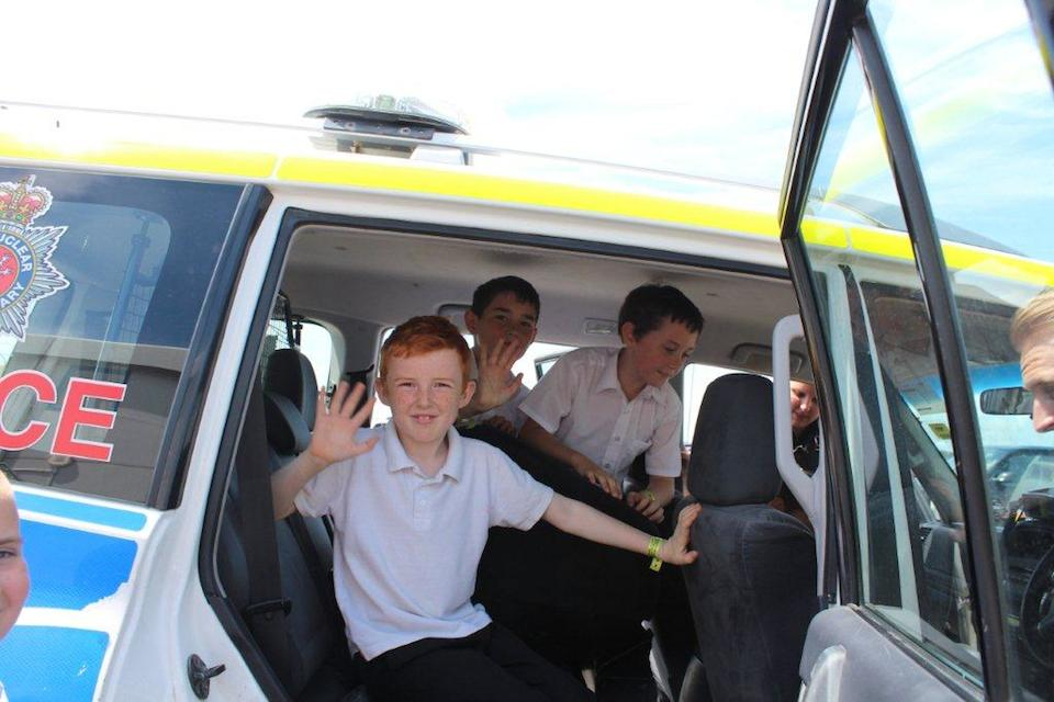 School children sat in police vehicle waving