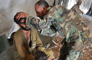 Afghan National Army Staff Sergeant Dur Mohammad treats a visitor to the Village Medical Outreach clinic
