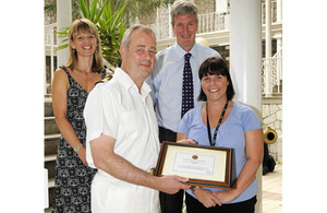 Commodore Adrian Bell presents Stacey Cooper with an award for her work in Afghanistan in 2009