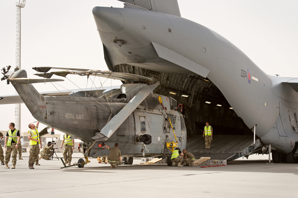 A Royal Navy Sea King helicopter being loaded onto an RAF C-17 aircraft