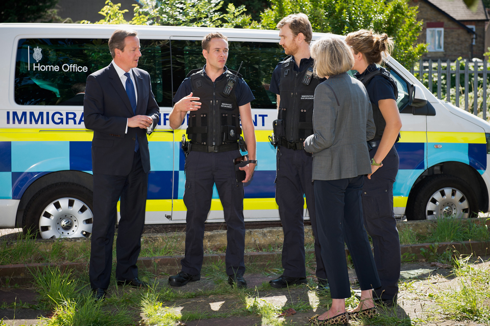Immigration officers explain their roles to David Cameron and Theresa May.