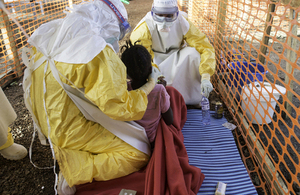 Doctors with Médecins Sans Frontières try to feed a young girl in the high contamination risk zone of a treatment centre in Sierra Leone. Picture: Sylvain Cherkaoui/Cosmos