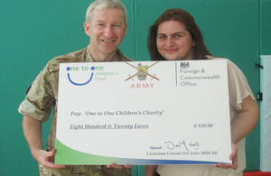 Lieutenant Colonel David Jones presenting a cheque to Liridona Zogaj, Project Director of One to One Children's Fund