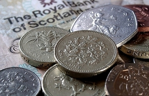 Pound coins along with Scottish bank note