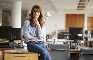 Woman sitting on a desk (credit: sZepy - Istock)