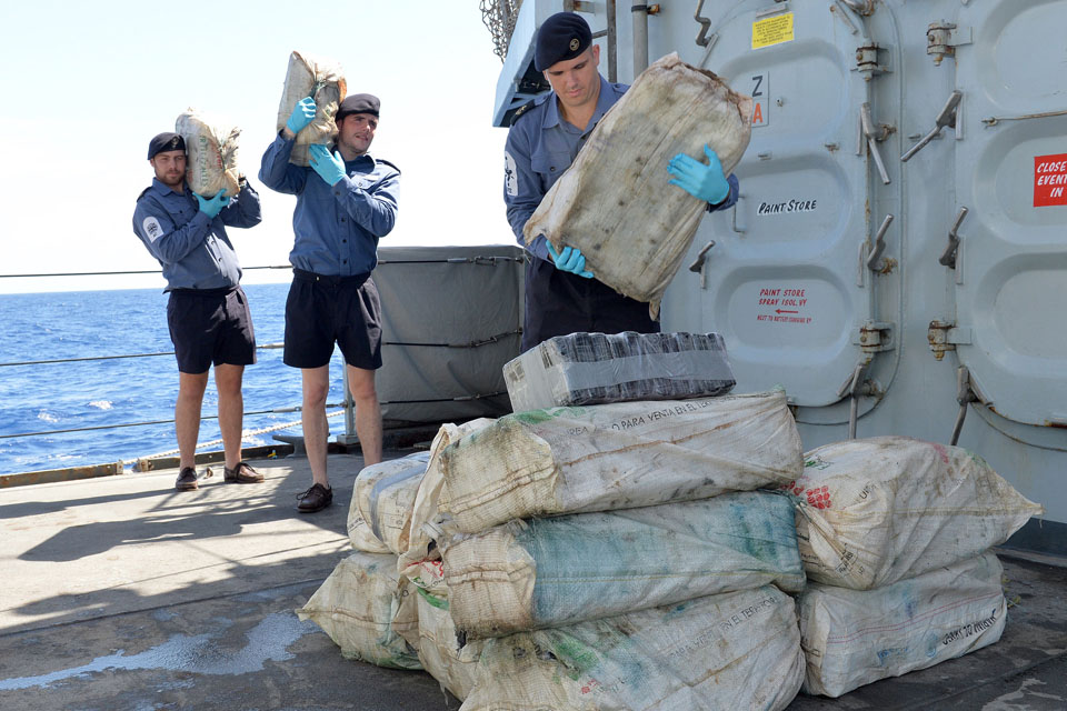 Royal Navy sailors transferring the seized cocaine to a US Coast Guard vessel