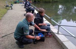 An Environment Agency officer helping a child fish