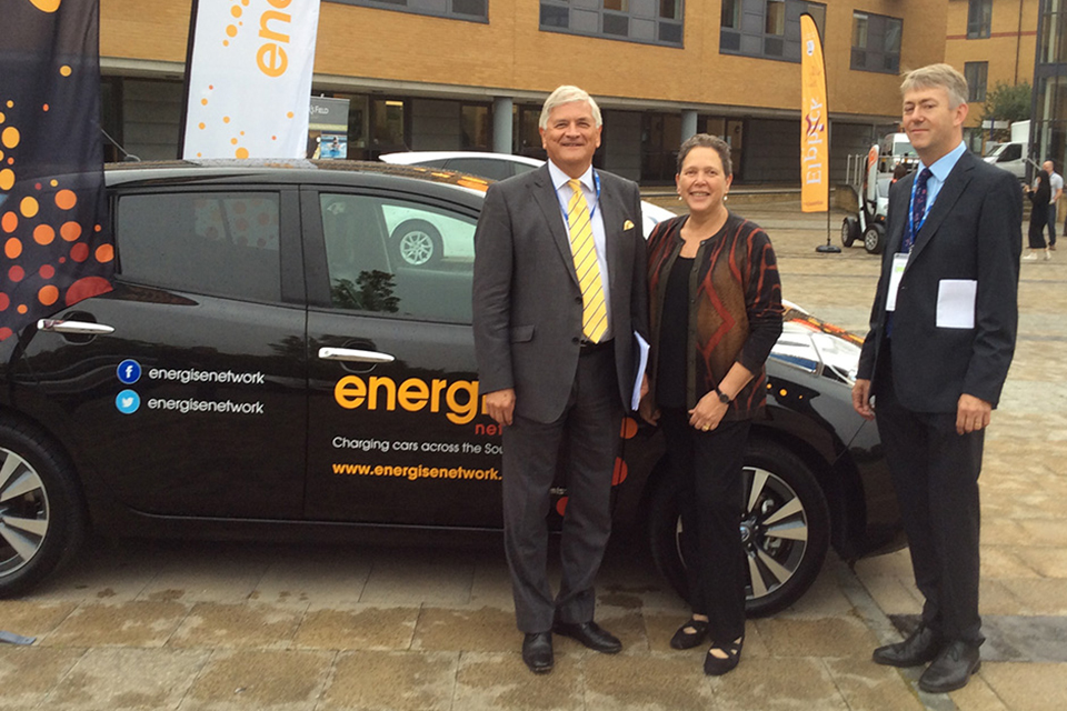 Baroness Kramer with attendees and green car.
