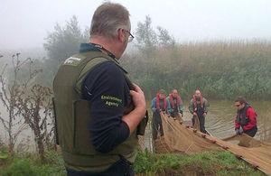 Environment Agency officers pull nets from the water