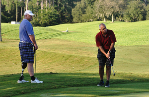 Zeno Gomes (right) playing golf as part of the Battle Back programme [Picture: Crown copyright]