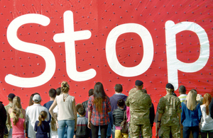 A group of people facing a big Stoptober sign in a red background
