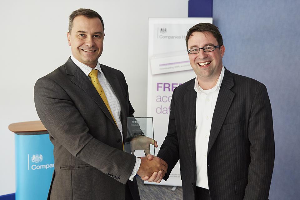 Photo of Tim Moss receiving award from John Turner