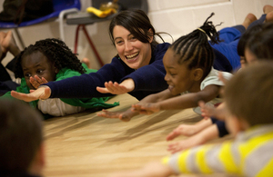 children and teaching assistant stretching on the floor