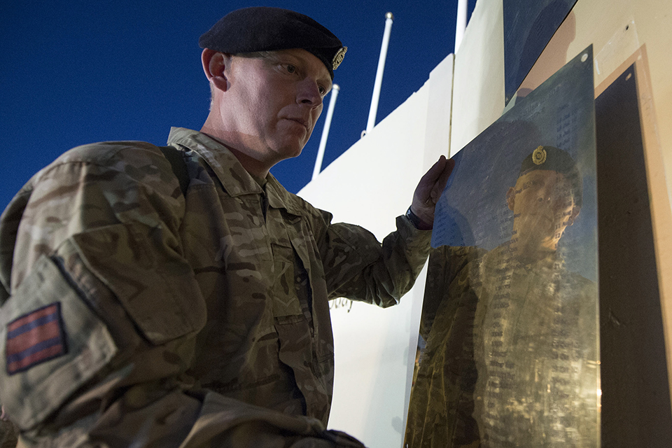 A name plaque is taken down from the memorial wall