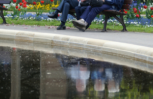 Three people sitting on a bench - their reflections displayed in a pond