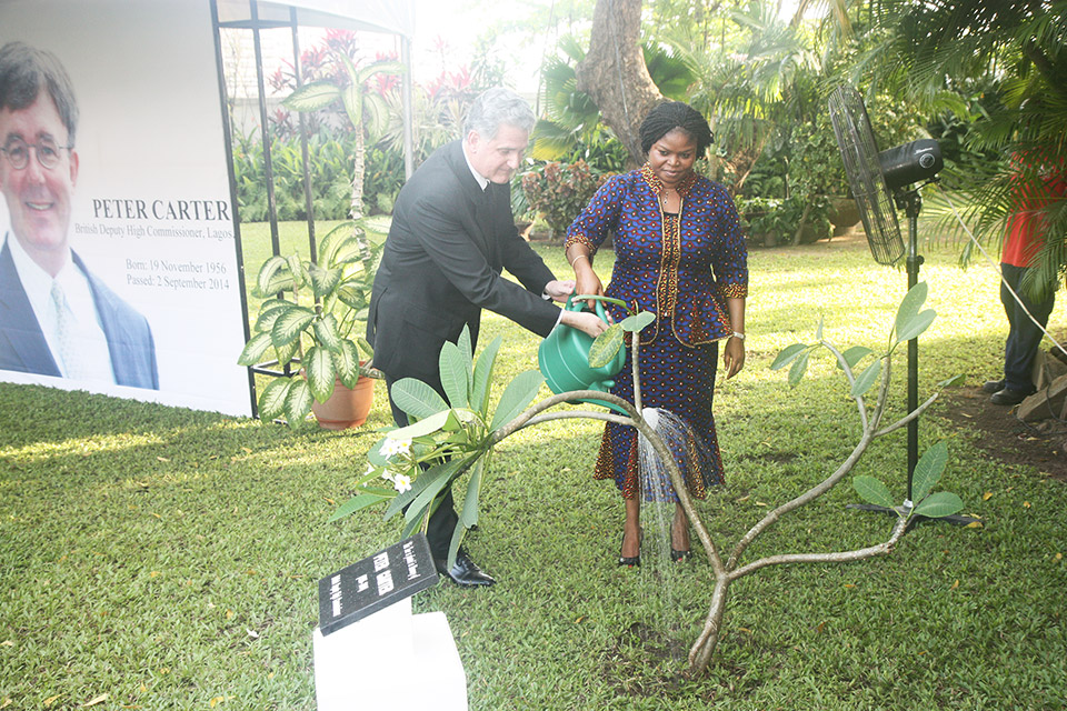 watering the tree planted in the garden of the British residence in honour of Peter Carter