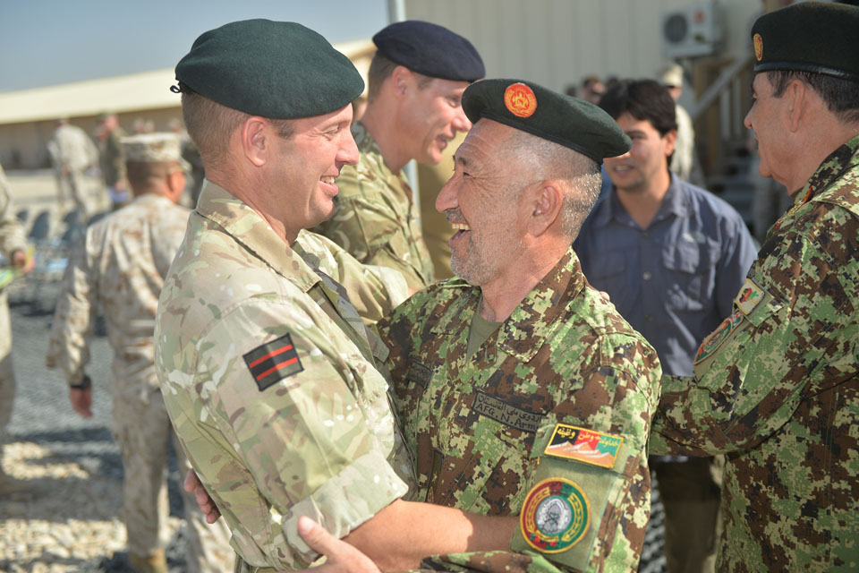 Brigadier Rob Thomson, Deputy Commander of Regional Command South West, embraces a senior Afghan official during the End of Operations Ceremony.