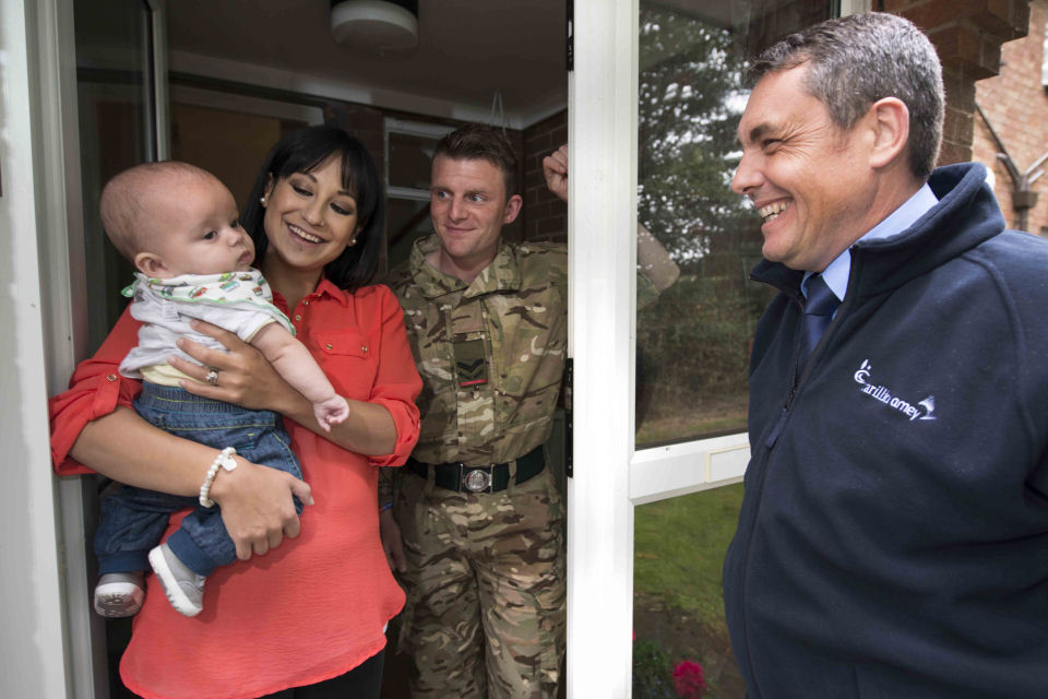 A CarillionAmey Accommodation Officer with a service family outside a service family accommodation property.