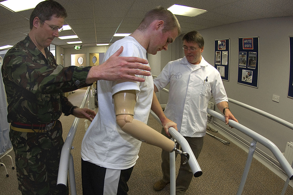 A soldier is guided in the use of his 3 prosthetic limbs at Headley Court
