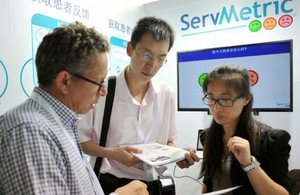 A UK participant from Servmetric discusses his services with Chinese visitors to the demonstration centre