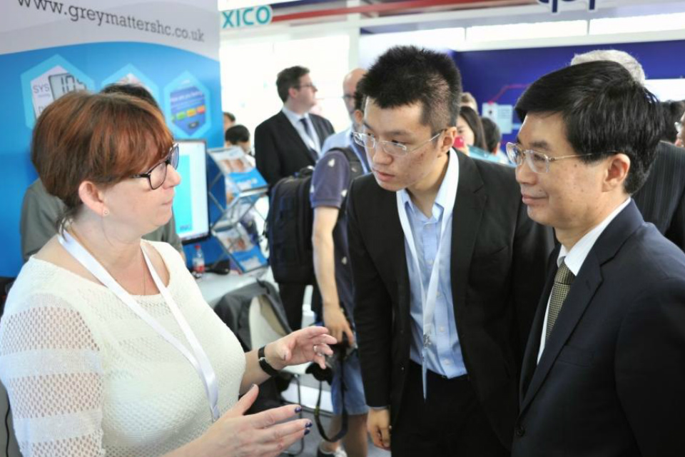 A UK participant from Grey Matters discusses her services with Chinese visitors to the demonstration centre