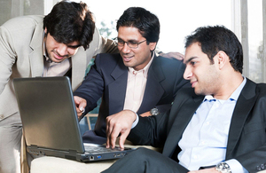 UK and Indian colleagues around a laptop