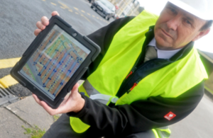 Man with laptop displaying highway data at roadside