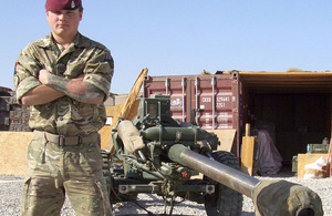 Gunner Jonathan Long poses alongside an L118 Light Gun in southern Afghanistan