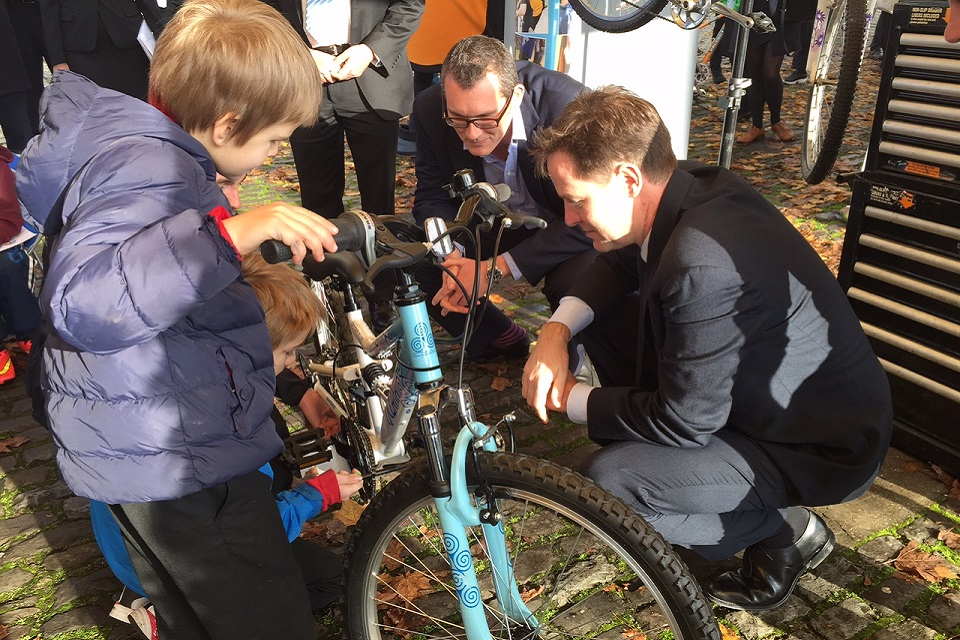 Nick Clegg, Halfords CEO Matt Davies & school children learning to maintain new bikes.