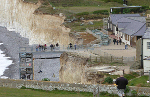 View of the sea and cliffs at Birling Gap in East Sussex where visitors are using the repaired steps to enjoy a walk on the beach