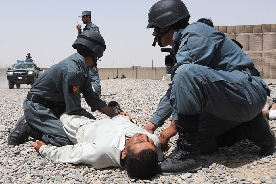 Afghan National Police recruits taking part in an exercise perform casualty drills in a mock Bazaar