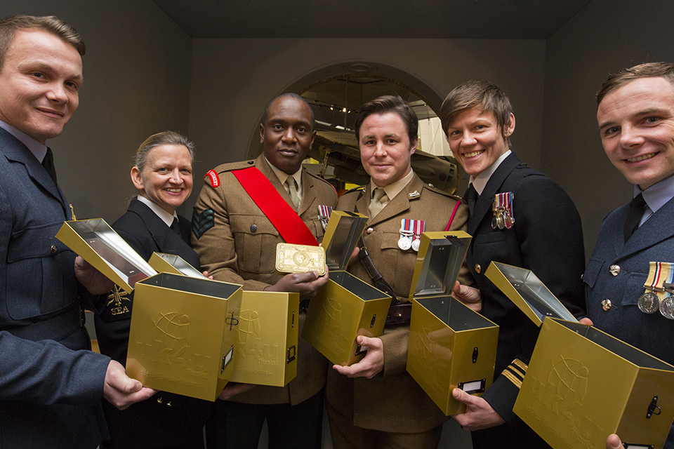 Service personnel with boxes from 1914 and today