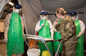 A soldier training Army reservists on how to don personal protective equipment in the fight against Ebola [Picture: Sergeant Si Longworth RLC, Crown copyright]