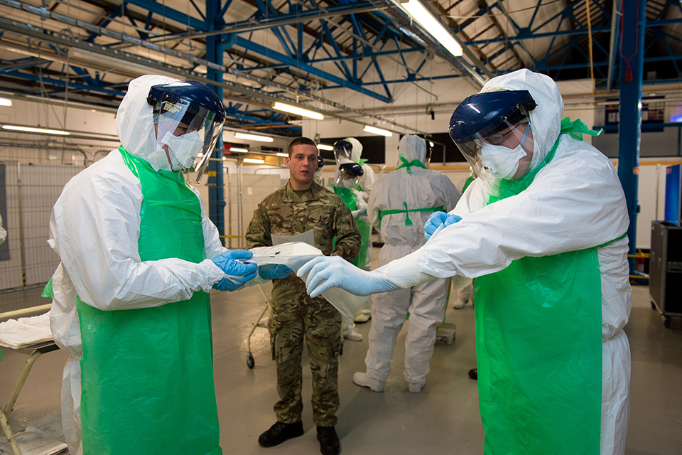 A soldier training Army reservists on how to don personal protective equipment