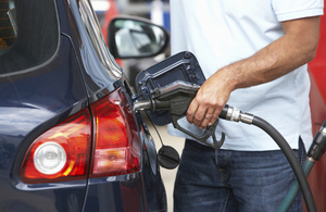 Photo of a person putting fuel in a car at a petrol station