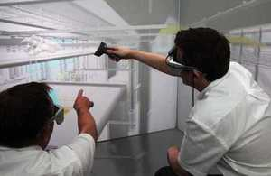 Two men wearing digital viewers to plan a factory project in a 3D visualisation suite