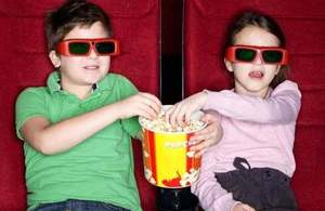 Two children in the cinema wearing digital specs and eating popcorn