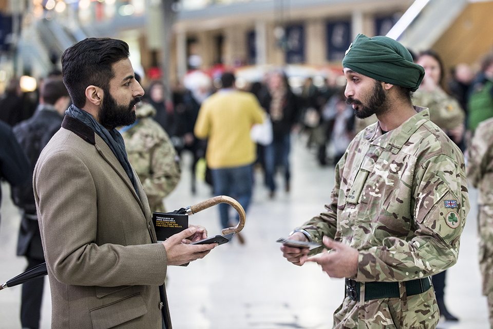 Rifleman Singh, 7 Rifles, talks to a member of public about joining the reserves.