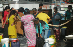 Nepalese people affected by flash flooding of the Seti River gather to collect fresh water provided by the British Gurkha Camp in Pokhara