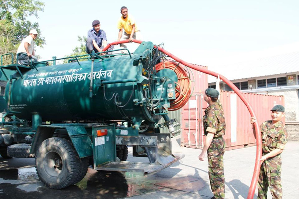 Gurkha soldiers at the British Gurkha Camp in Pokhara fill a local authority water tanker to help local Nepalese people affected by flash flooding of the Seti River