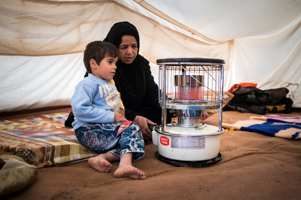 Warda and one of her children keep warm by a stove heater heater in their tent in northern Iraq. Picture: Andrew McConnell/Panos for DFID