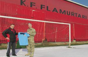 Lieutenant Colonel David Jones presenting the football strips to Mr Fatmir Ibrahimi, Football Club Flamurtari Youth Team coach