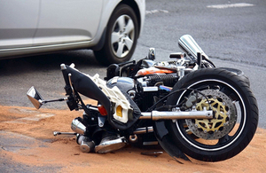 Image of a damaged motorcycle by a car