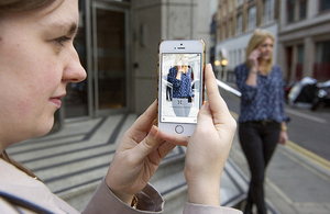 Image of Jenny Lewis, founder of Snap Fashion taking a picture of a passer by with a mobile phone.