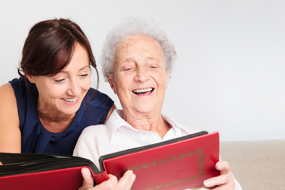 middle aged woman and older woman with photo album