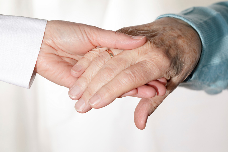 a young person and an old person holding hands