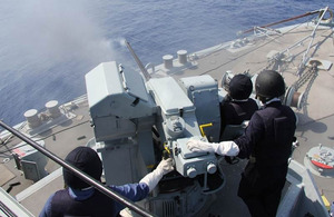 Sailors onboard HMS Bangor fire the ship's gun